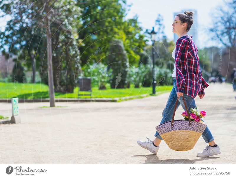 Side view of a young hipster woman holding a wicker basket while walking in a park in sunny day Profile Young woman Hipster Hold Wicker basket Basket Walking