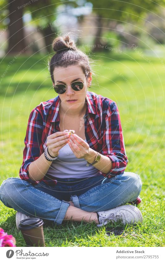 Front view of a young hipster woman sitting on grass in a park while holding a flower in a sunny day Young woman Hipster Hip & trendy Sit Hold Flower Park Grass