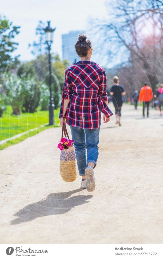 Rear view of a young hipster woman walking in a park in sunny day while holding a wicked basket Woman Young woman Hipster Walking Hip & trendy Park Relaxation
