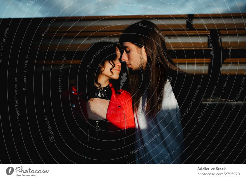 Long haired man and woman standing near train Couple abandoned wagons Embrace Railroad Graffiti old train Kissing Love Engines Hipster Youth (Young adults)