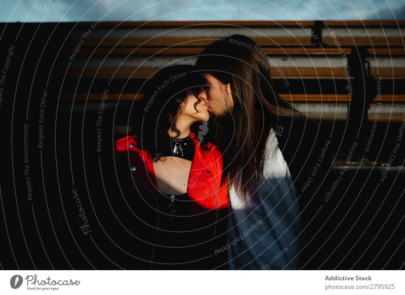 Long haired man hugging and kissing woman near train Couple Embrace Railroad Graffiti Kissing Love Engines