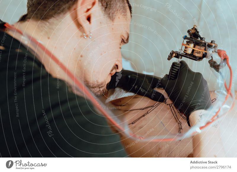 Stylish woman making tattoo Man Tattoo Artist Client Studio shot Tool Drawing Piercing