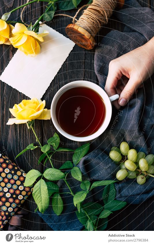 Crop hand with tea near flowers and blank note Hand Rose Tea Blank Table Cloth Bunch of grapes Thread Surprise Gift Cup Drinking Beverage Hot Fresh Flower