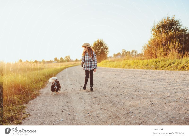 happy child girl walking country road with her dog Lifestyle Joy Leisure and hobbies Playing Vacation & Travel Trip Adventure Freedom Expedition Summer Hiking