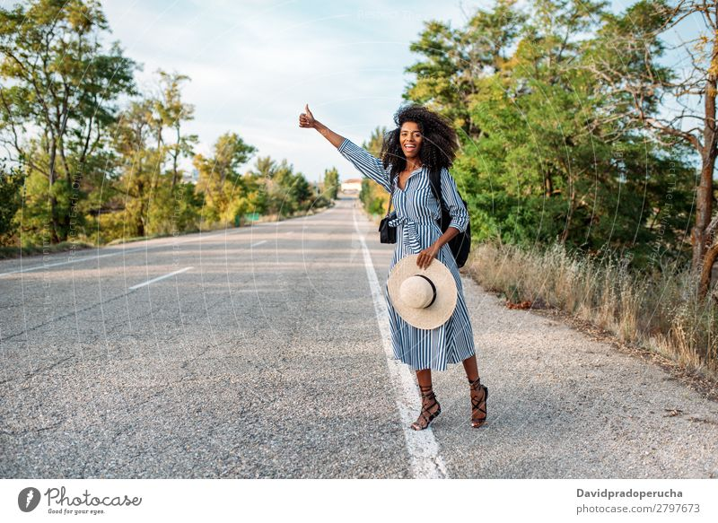 Happy black woman hitchhiking with thumbs up Woman Vacation & Travel Backpacking Ethnic Adventure Street Lift Hitchhike auto stop Trip Black Smiling African