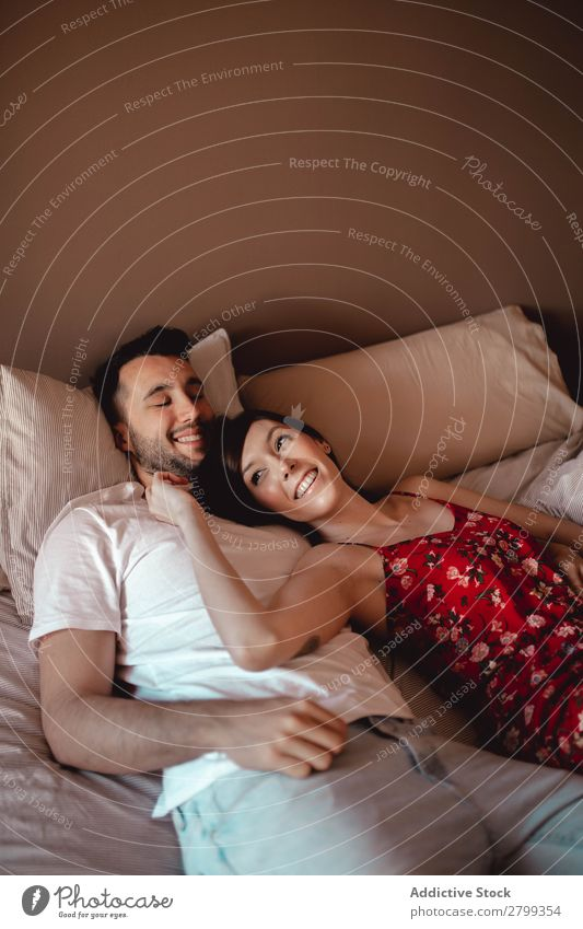Happy couple cuddling on bed Couple Smiling Bed Home Man Woman Love Cuddling