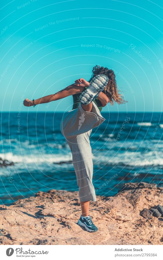 Anonymous female kicking air on seashore Woman Ocean Coast Sky Blue Beautiful weather Lifestyle Leisure and hobbies Waves Stone Water Movement Practice Balance