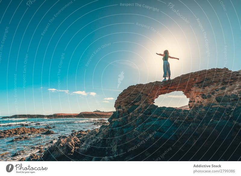 Anonymous woman with outstretched arms on cliff near sea Woman Freedom Cliff Ocean Lifestyle Leisure and hobbies Rest Relaxation Waves Coast Sunbeam Day Water