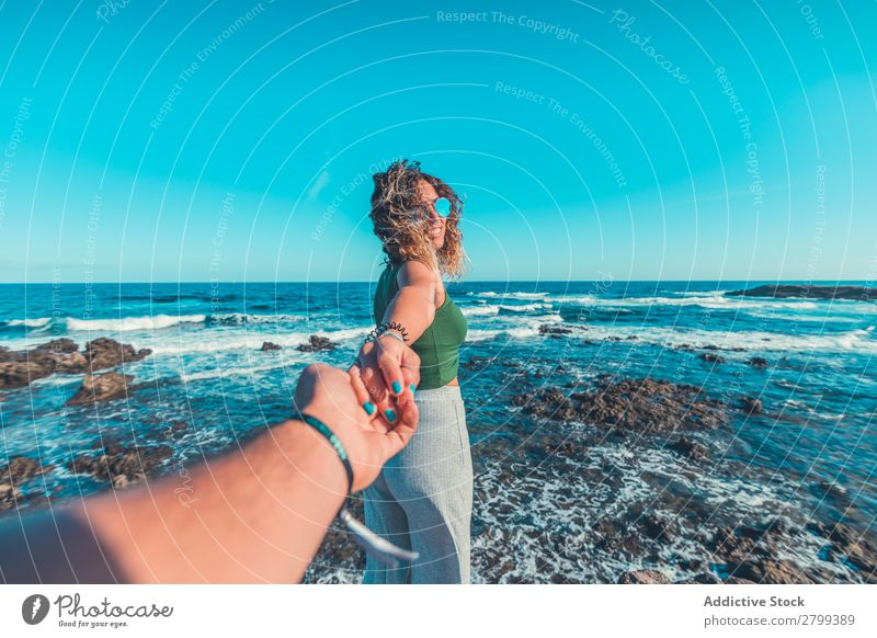 Smiling woman offering to follow her near sea Woman Ocean follow me Hand Friendship Coast Lifestyle Leisure and hobbies Rest Relaxation Waves Water Style