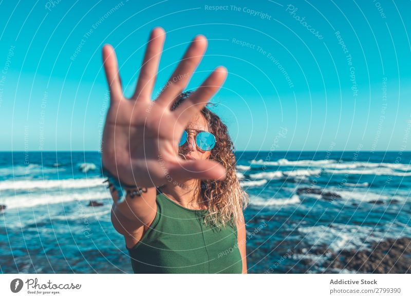 Woman gesturing stop near sea Stop Gesture Ocean Coast Lifestyle Leisure and hobbies Rest Relaxation Waves Sunbeam Palm of the hand Day Refuse Water Style
