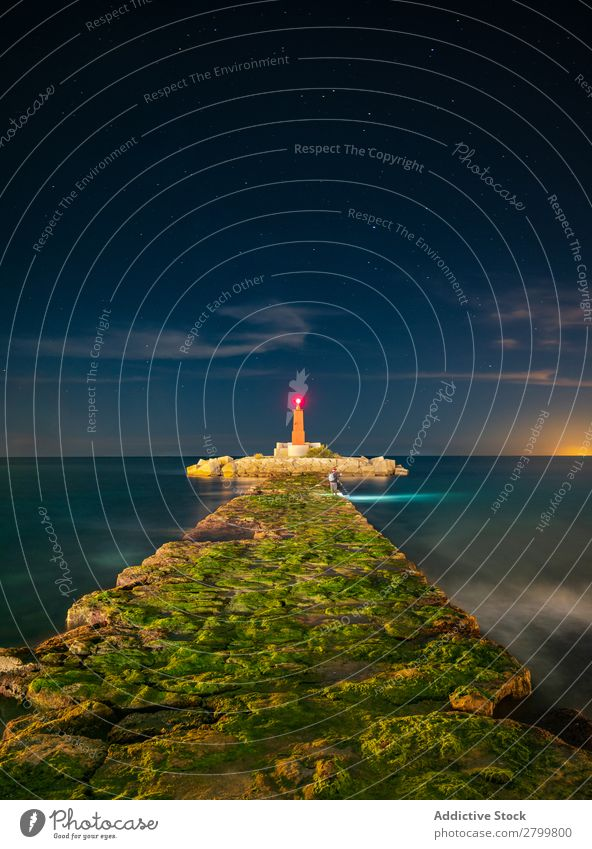 Rough path to bright beacon in evening Lanes & trails Lighthouse Ocean islet Evening Stone Sky Vacation & Travel Water faro villajoyosa Spain shine Damage way