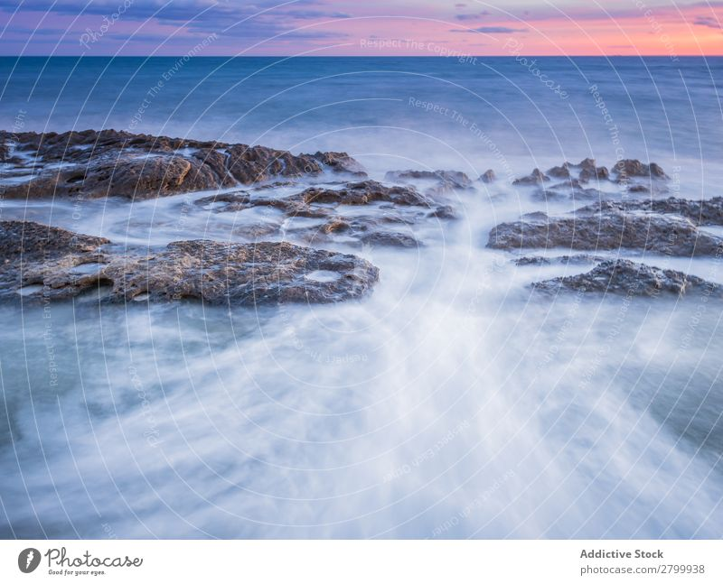 Sea waving near rough rocks during sunset Ocean Rock Waves Sunset Evening Sky Clouds Nature seascape Water Stone Rough rolling Splash Landscape Power Foam