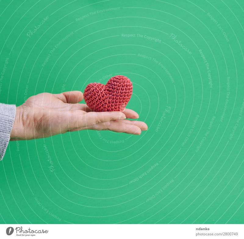 small knitted red heart in a human hand Decoration Feasts & Celebrations Valentine's Day Wedding Hand Heart Love Green Red Romance Colour background Card