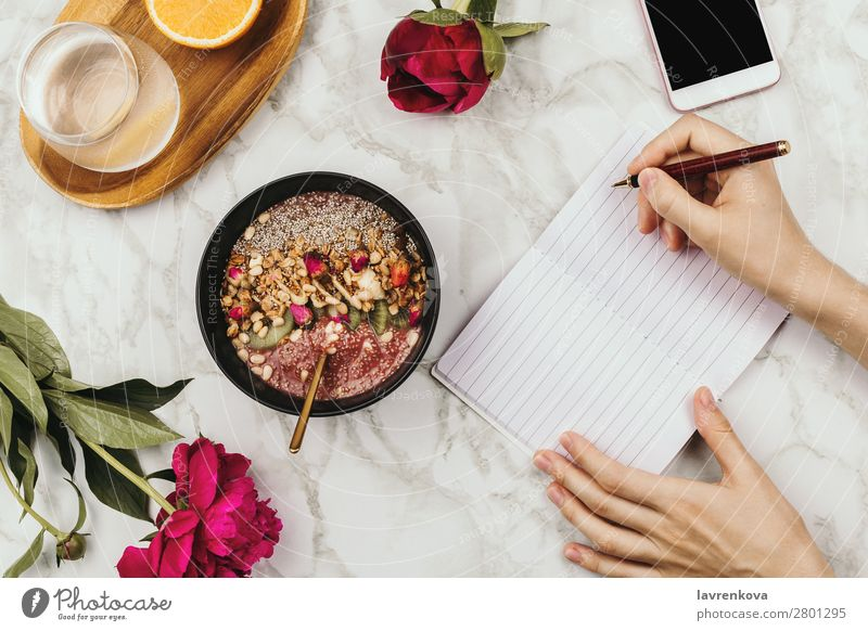 Flatlay of woman's hands with notebook and smartphone, vegan smoothie bowl with chia pudding PDA Organic Ingredients Pen Vantage point Top Marble Snack topping