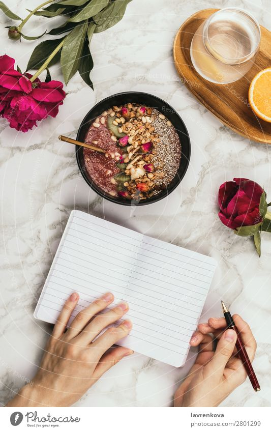 Hands holding smoothie bowl with notebook, peonies and water Organic Ingredients Pen Vantage point Top Marble Snack topping Cereal lay flat Flower flatlay Table