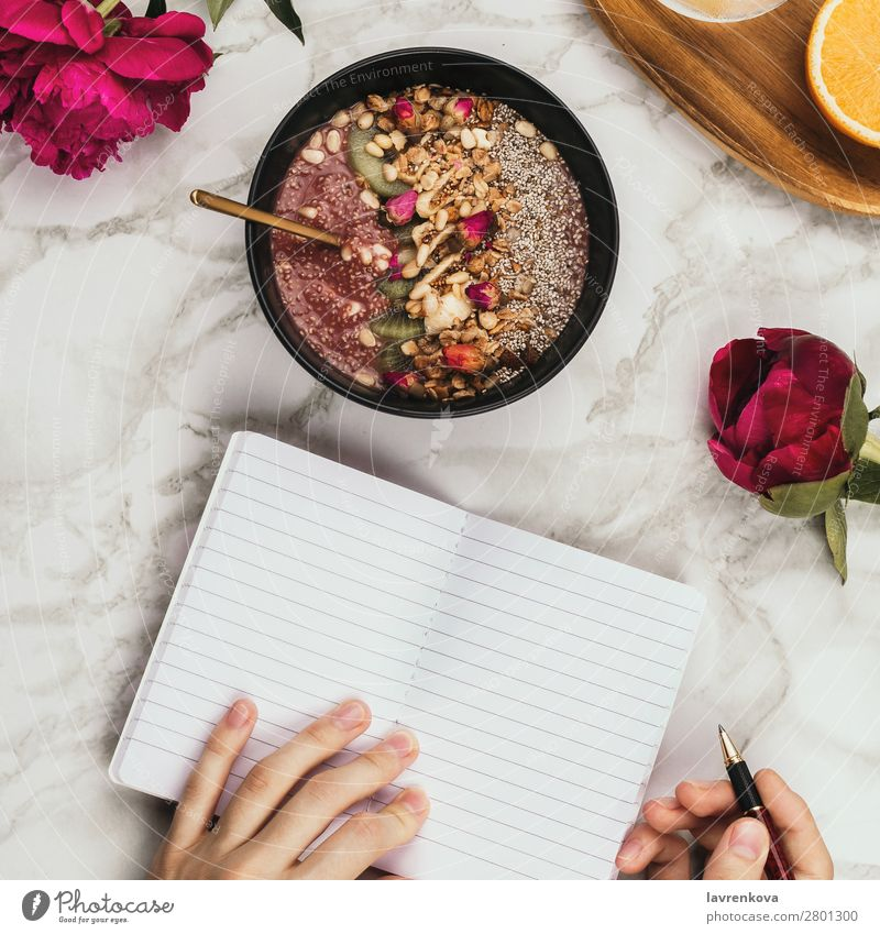 Woman's hands with notebook, smartphone and smoothie bowl square Pen Vantage point Top Marble Snack topping Cereal lay flat Flower flatlay Table Peony Water