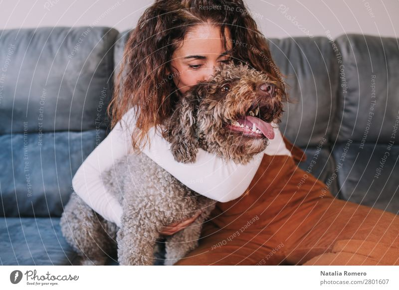 A pretty girl hugs her pet while kissing her Woman Human being Dog Youth (Young adults) Young woman Beautiful House (Residential Structure) Relaxation Animal