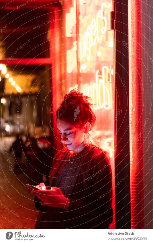 Attractive stylish lady using smartphone near neon lights Woman Style PDA Hip & trendy Neon Tel Aviv Israel Cellphone