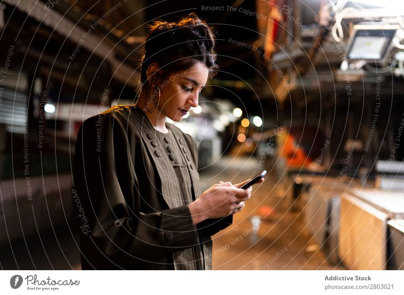 Stylish lady with smartphone on closed market at night Woman Style Markets PDA Hipster Night Tel Aviv Israel Street Cellphone using small shop Closed