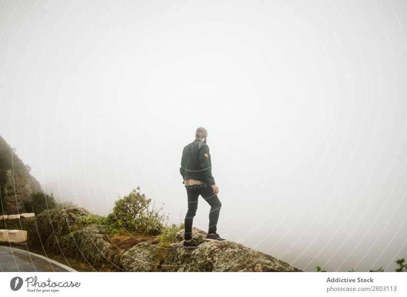 Anonymous man standing on cliff near countryside road Man Fog Landscape Street Cliff Spain playa norte Rock Vacation & Travel explore admiring Weather Trip