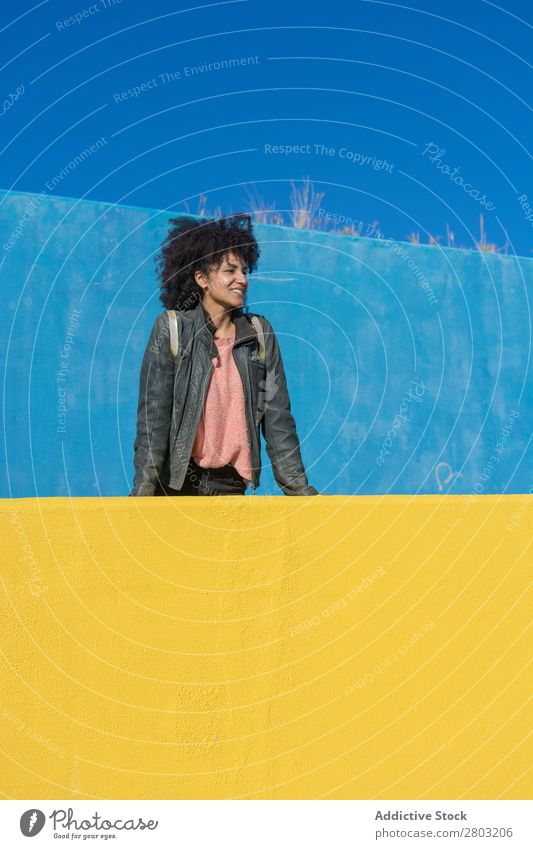 Black woman with afro hair leaning against brightly colored walls. Adults African Afro American Background picture Beautiful Beauty Photography Blue Easygoing