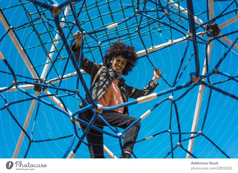 Woman with afro hair climbing by children's attractions. Action African Afro Black Cheerful Infancy Climbing Cute Equipment Family & Relations Joy Girl Happy