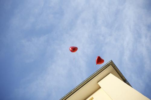 Love is in the air Sky Clouds Beautiful weather Town House (Residential Structure) Wall (barrier) Wall (building) Facade Roof Eaves Blue Yellow Red Balloon