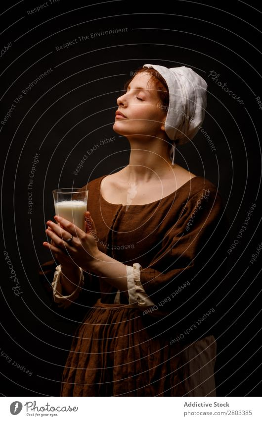 Medieval maid with glass of milk Red-haired Milk Glass Woman Closed eyes Clothing Dress Costume
