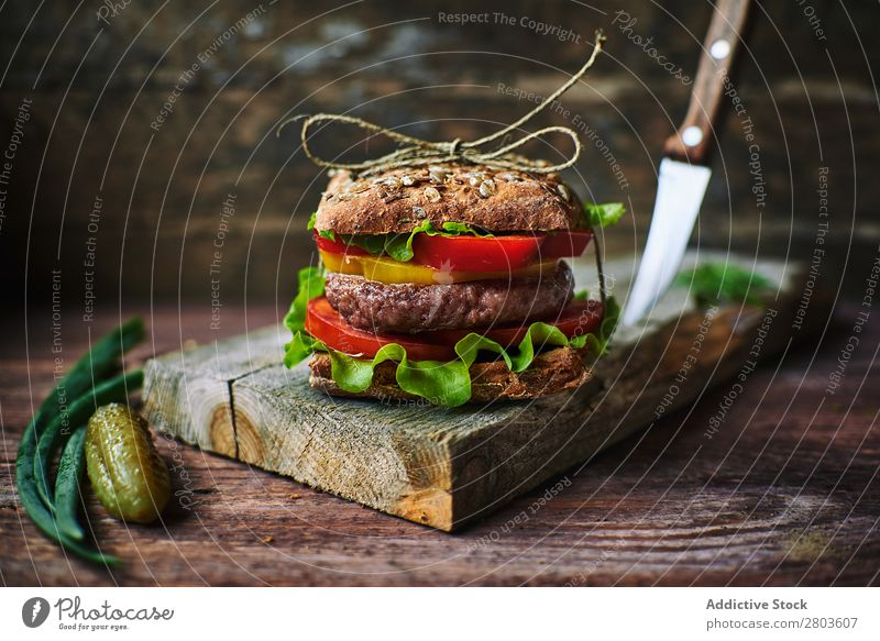 Delicious burger on wooden board Food Board Onion Pickles Preparation Lunch Cooking Meal Roll Speed Gourmet Unhealthy Bread tied Thread Rustic Tasty yummy