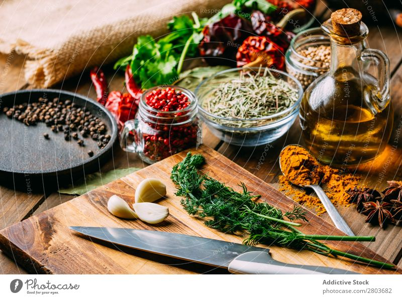 Spices and oil near knife Herbs and spices Oil Knives Table assortment Cooking Ingredients Set Fresh Dill Parsley Garlic anise turmeric Cardamom Coriander Chili