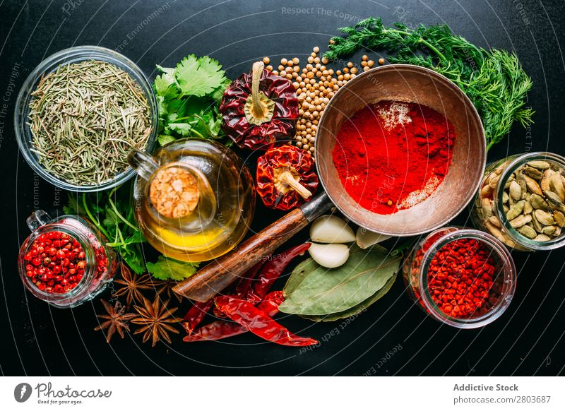 Assorted spices near fresh oil Herbs and spices Oil assortment Cooking Ingredients Set Fresh Dill Parsley Garlic anise Cardamom Coriander Chili pink pepper