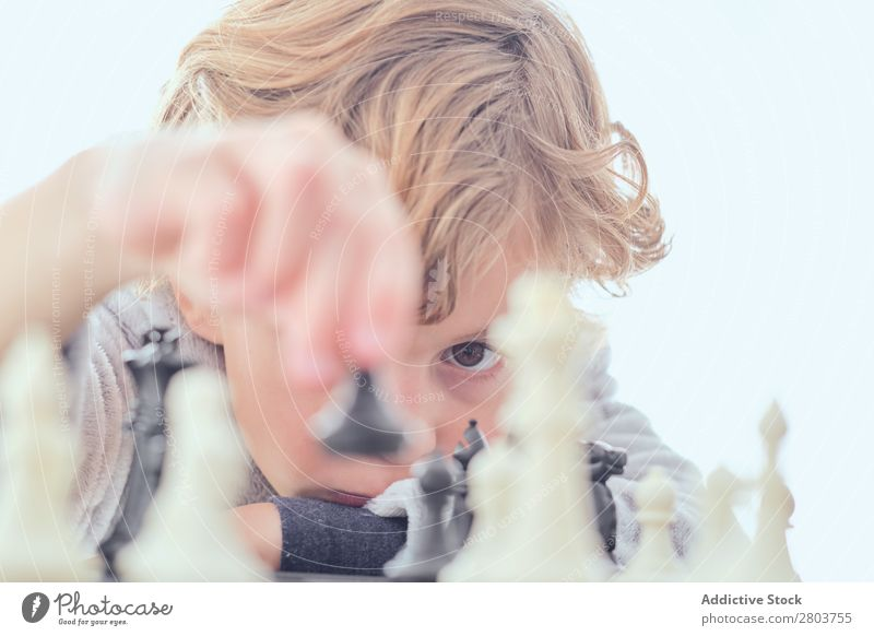 Boy holding figure on chess board Boy (child) Blonde Chess Chessboard Figure Table Playing Smart Indicate Child White Curtain Joy Leisure and hobbies Intellect