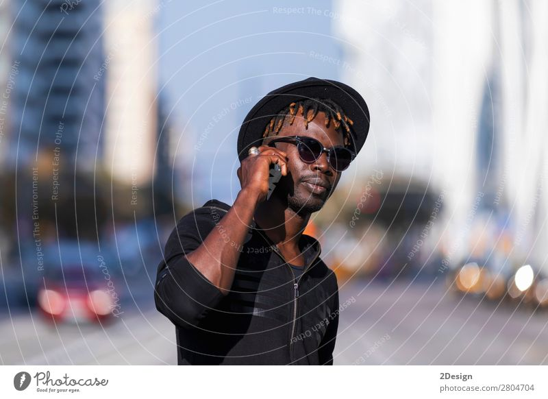 Front view of black man with sunglasses and hat standing Lifestyle Style Happy Leisure and hobbies To talk Telephone PDA Technology Human being Masculine