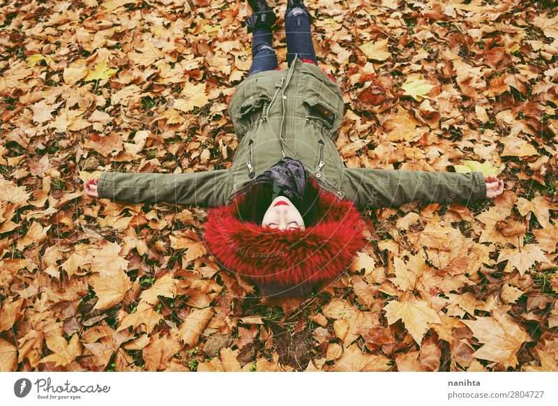 Young brunette woman lying down over autumn leaves Lifestyle Style Face Healthy Wellness Well-being Relaxation Calm Leisure and hobbies Human being Feminine