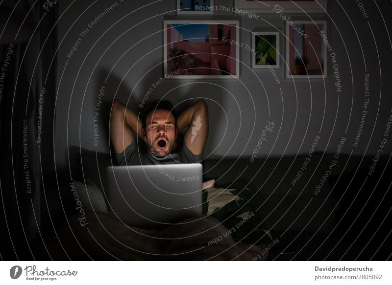 Man in pajamas with a computer yawning Adults Attractive Beautiful Boy (child) Caucasian Comfortable Communication Computer Copy Space Couch Cozy Dark device