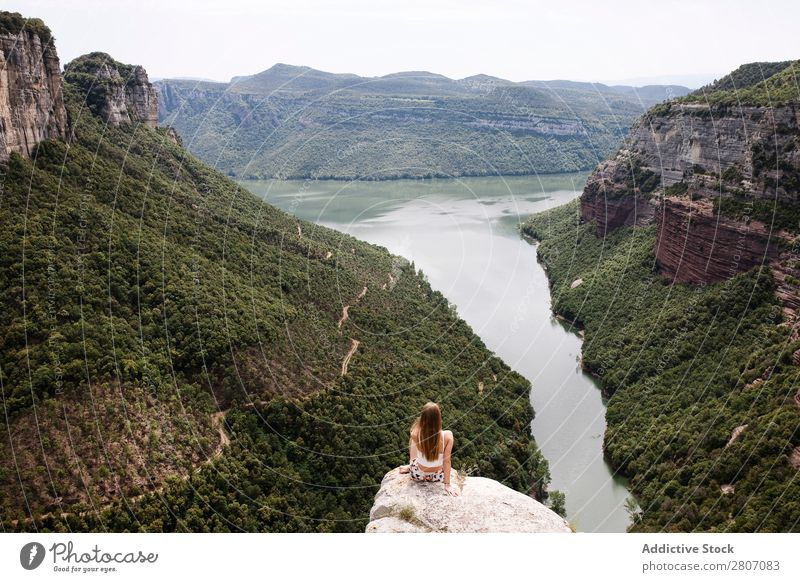 Young woman sitting on edge of cliff Woman Cliff Edge Sit Lake Nature Vacation & Travel Youth (Young adults) Rock Landscape Freedom Adventure Hiking Mountain