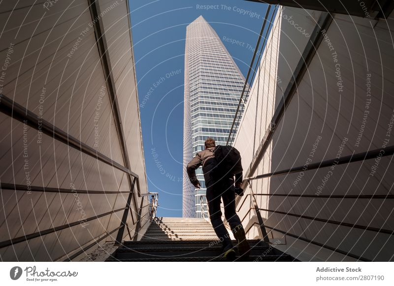 Man climbing the stairs to the skyscraper - 4 Stairs Office City High-rise Human being Exterior Modern Business center up Madrid Success Town Skyline Spain