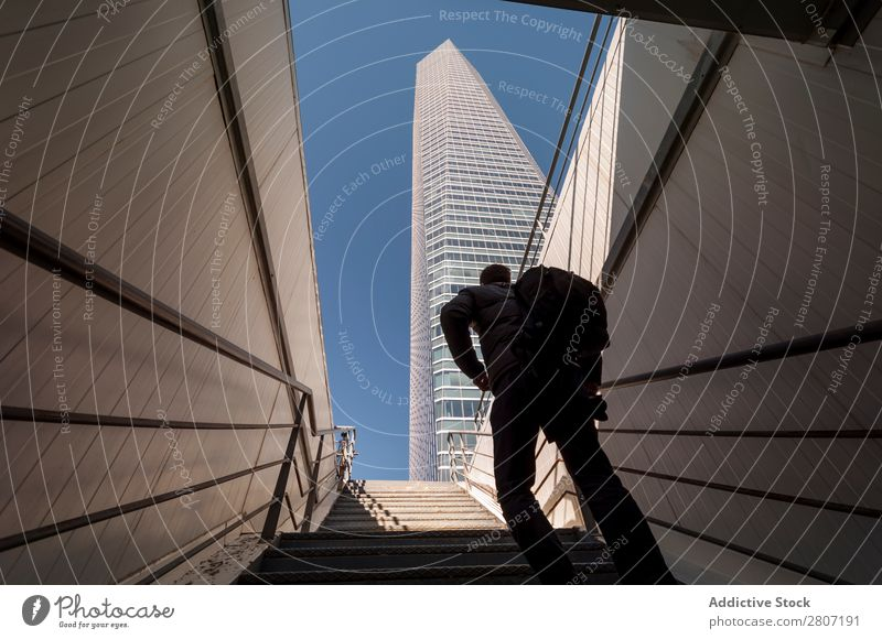 Man climbing the stairs to the skyscraper - 2 Stairs Office City High-rise Human being Exterior Modern Business center up Madrid Success Town Skyline Spain