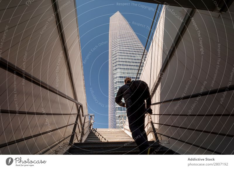 Man climbing the stairs to the skyscraper - 3 Stairs Office City High-rise Human being Exterior Modern Business center up Madrid Success Town Skyline Spain