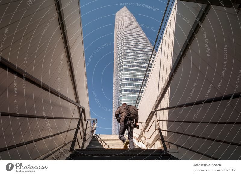 Man climbing the stairs to the skyscraper - 8 Stairs Office City High-rise Human being Exterior Modern Business center up Madrid Success Town Skyline Spain