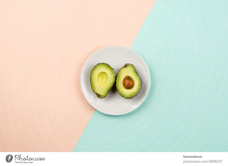 Cut avocado on white plate on pastel background Slice Natural Raw Fresh Green Mature Organic Nutrition Vegetarian diet Vegan diet Fruit Eating flat lay Plate