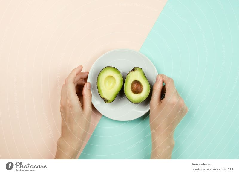 Cut avocado on white plate and woman's hands Vegetarian diet Vegan diet Fruit Eating flat lay Plate Ingredients Diet Healthy Healthy Eating Pastel tone Woman