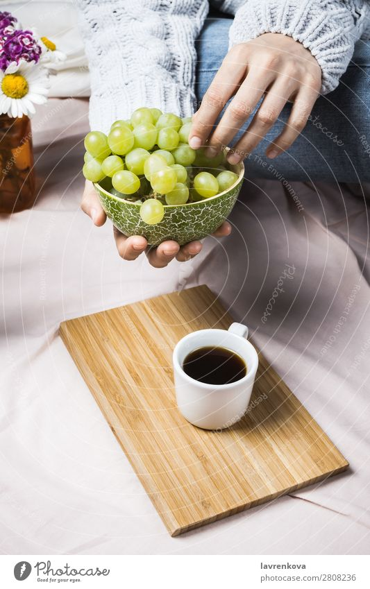 Woman's hands in sweater holding wooden bowl with grapes Autumn Harvest Cozy Natural Summer Fresh Close-up Fruit Organic Mature Eating Bed Bedclothes Blanket