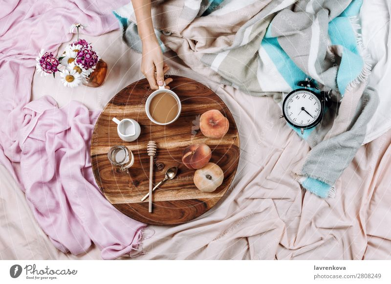Cozy flatlay of wooden tray with cup of coffee, peaches, creamer Alarm clock Morning Cup Mug flat lay Bedroom Breakfast Espresso Syrup Spoon Fruit Peach Bouquet