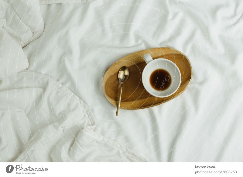 Cup of coffee and spoon on wooden tray in bed on white sheets Spoon Wood Tray Bedroom Espresso Healthy Healthy Eating holiday Tea Beverage Black Hot Morning