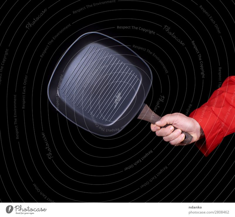 hand is holding a black empty square grill pan Pan Kitchen Restaurant Profession Cook Tool Man Adults Hand Metal Steel To hold on New Red Black Cast iron