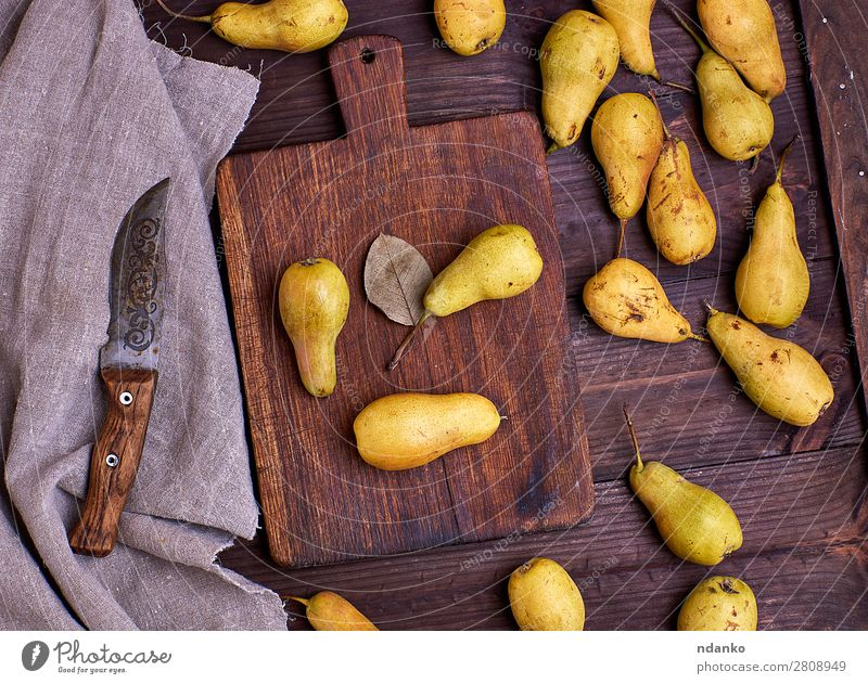 pears scattered on a brown wooden table Fruit Nutrition Vegetarian diet Diet Table Wood Old Eating Fresh Delicious Natural Above Brown Yellow Green board