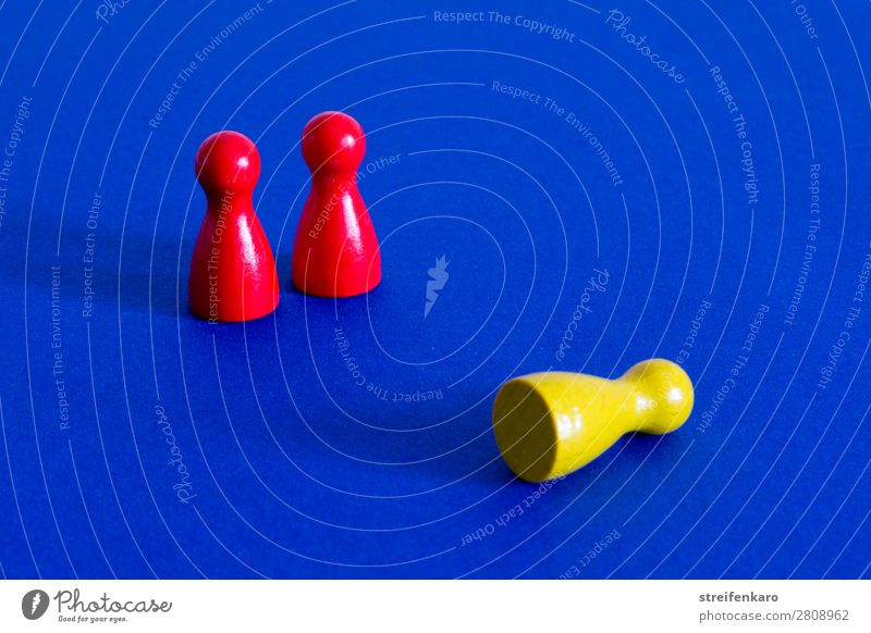 A yellow playing piece lies in front of two standing red playing pieces on a blue background Economy Business Company Success Team Toys Wood To fall Hunting