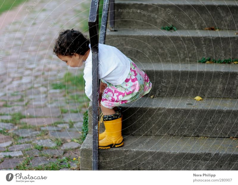 being insouciant Playing Child Human being Feminine Girl Infancy Body 1 1 - 3 years Toddler Stairs Cobblestones Handrail Rubber boots Black-haired Movement