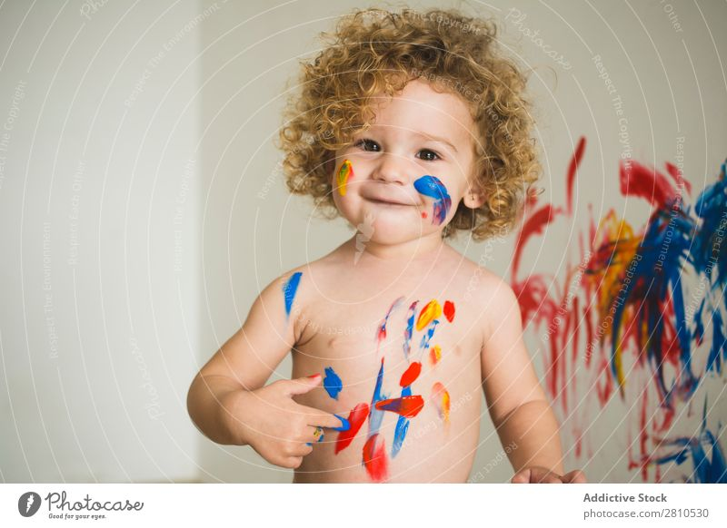 Cheerful kid painting on body Child Painting (action, artwork) Small Draw Joy Smiling Looking into the camera Delightful Bright Body Art Drawing Infancy Colour